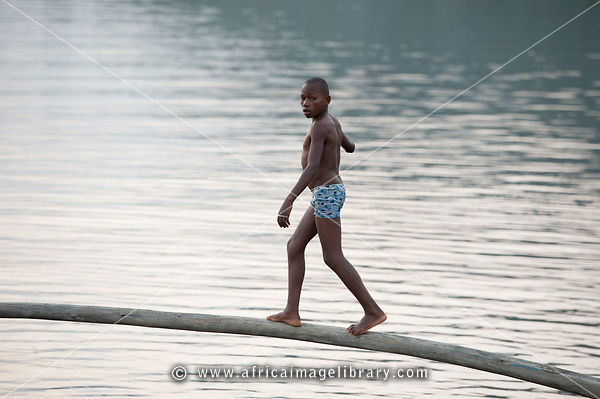 Boy playing between the fishing boats on Lake Kivu, Rubavu, Rwanda