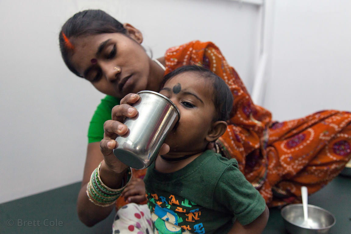 A mother gives her boy a drink at a clinic operated by Calcutta Kids (calcuttakids.org) in Howrah, India