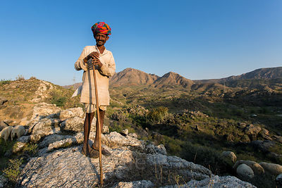 Sheep herder in the desert surrounded by the Aravali Range, Ajaypal, Rajasthan, India