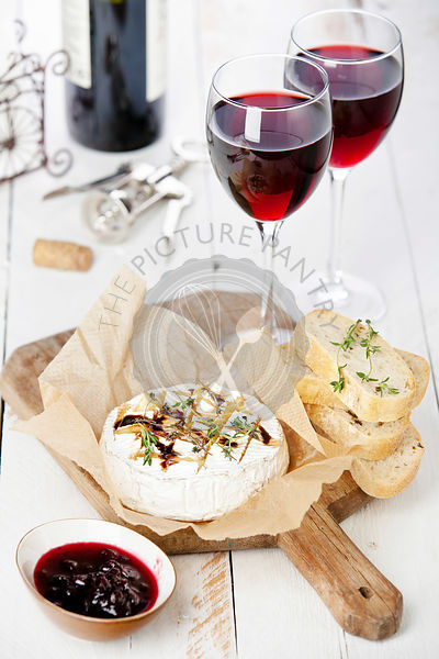 Baked Camembert cheese with red wine and toasted bread on wooden board