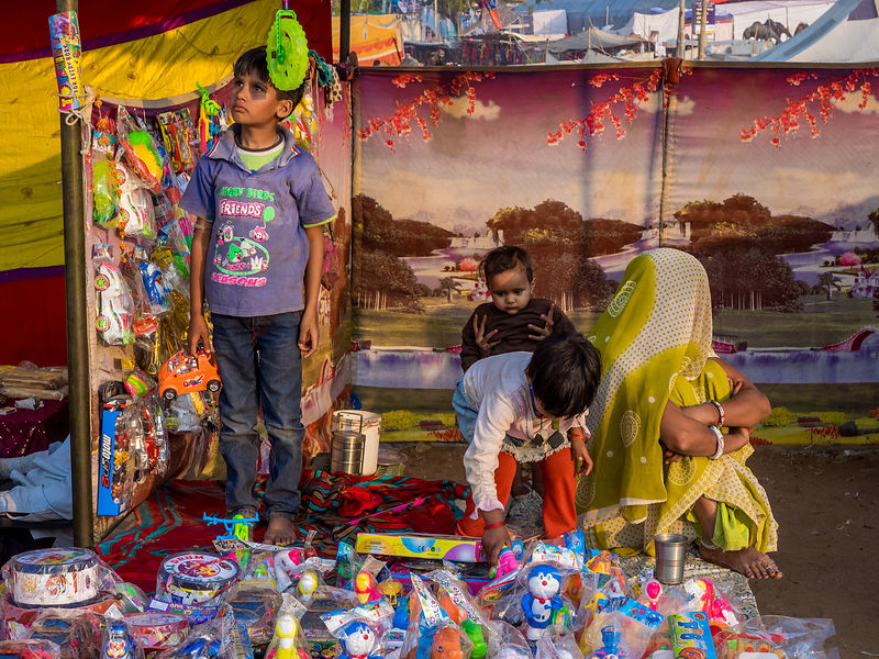 A woman vendor with her kids wait for the customers, during the Pushkar camel fair
