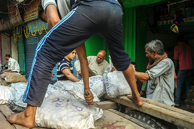 Men Unload Sacks Of Onions From A Cart