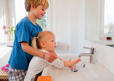 Brother and sister washing their hands