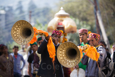 Men blow large brass horns during the celebration of Dussehra in Kullu, India