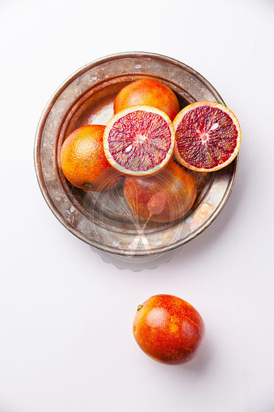 Ripe red oranges on white textured background