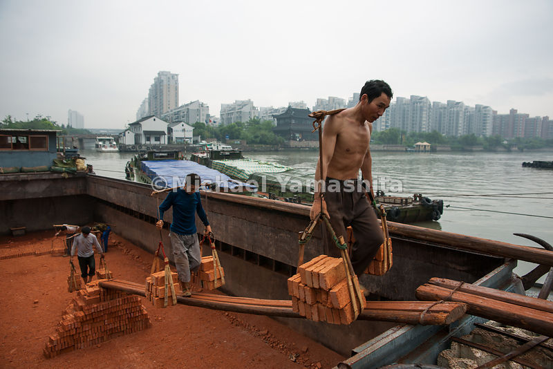 The load of bricks that each stickman carries weighs about 200 pounds. The porters, at Beixinqiao dock in Hangzhou, get the n...
