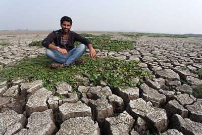An NGO worker sits on parched and deeply cracked land in the East Kolkata Wetlands, Kolkata, India.