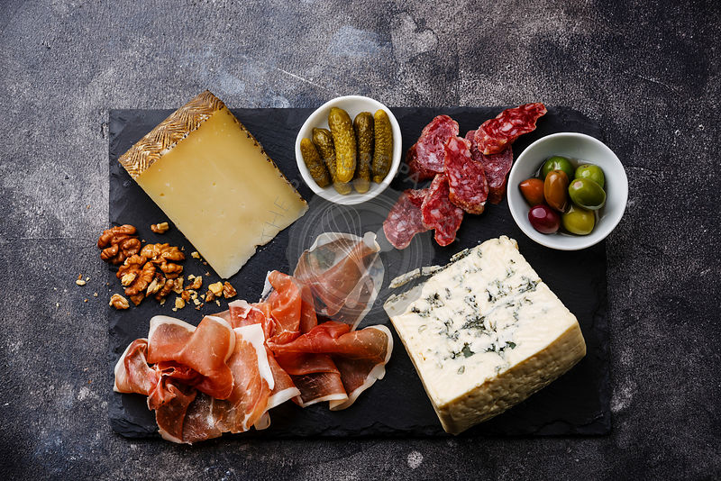 Italian snacks food with Prosciutto, Olive, Cheese and Sausage on dark background