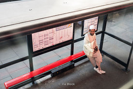An Arabic man sitting on a bench at a bus stop in London, UK.