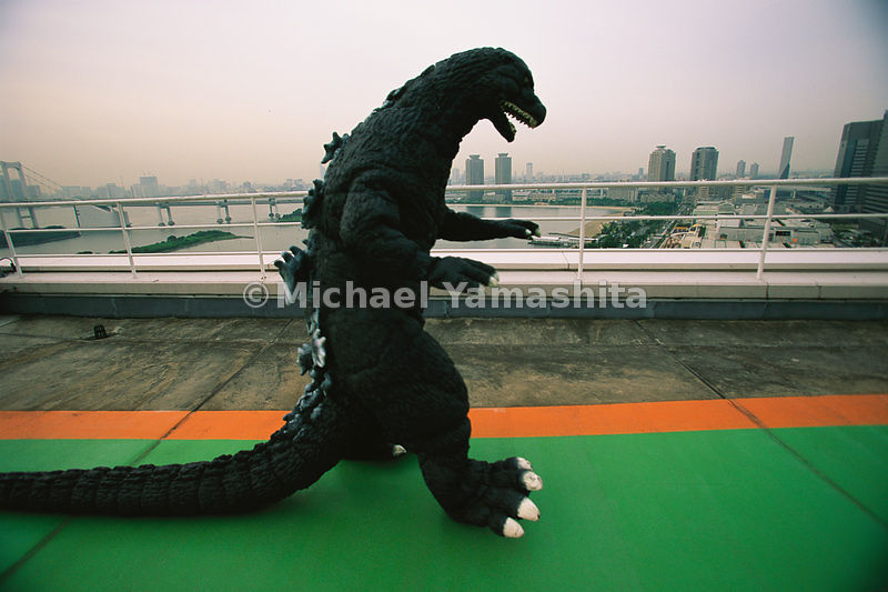 Monstrous sprwal makes for a smoggy backdrop behind costume-clad actor Kenpachiro Satsuma who once played the movie menace Go...