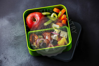 Take out food Greek salad and Apple fruit in Lunch box on blackboard background