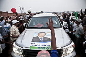 Supporters of presidential candidate Robinson Jean Louis cheer arounf his car during the last campaign rally on October 23, 2013 in Antananarivo ahead of the presidential elections on October 25, 2013. Thirty-three candidates are running in a poll that is meant to end a four-year political crisis on the Indian Ocean island sparked when strongman Andry Rajoelina ousted then-president Marc Ravalomanana in a coup. But supporters are divided over new candidates after Rajoelina and Ravalomanana's wife Lalao, along with a few others, were barred from running under international pressure. After the presidential polls, a parliamentary vote will follow on December 20, along with a second presidential round if the October election does not deliver an outright winner. Madagascar votes on October 25 in long-delayed elections meant to pull the island nation out of a devastating political crisis that plunged millions into misery after the 2009 coup.