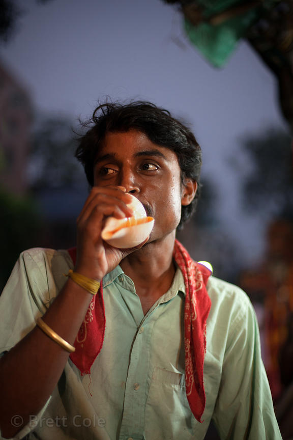 A man blows a conch shell at a market in Kalighat, Kolkata, India. The shells are used in various Hindu religious rituals.