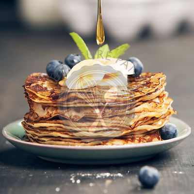 Pancake tower with fresh bananas, blueberries and honey on a rustic table