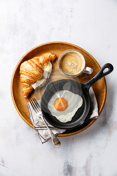 Breakfast with Fried egg on iron pan, croissant sandwich with cheese and ham and coffee on wooden tray on white background