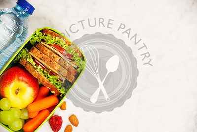 Healthy school lunch box with sandwich, apple, grape, carrot and bottle of water close up on white wooden  background.
