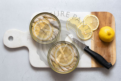 Two cans of sardines in oil with slices of fresh lemon.