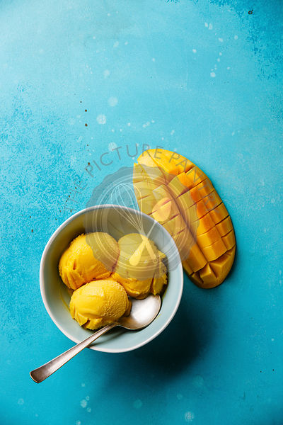 Mango ice cream sorbet and Fresh mango on blue background copy space