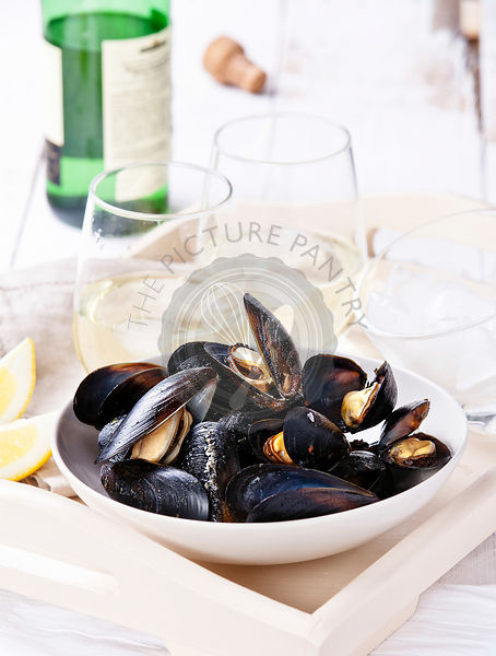 Mussels and clams served in white bowl with glasses of white wine and piece of lemon