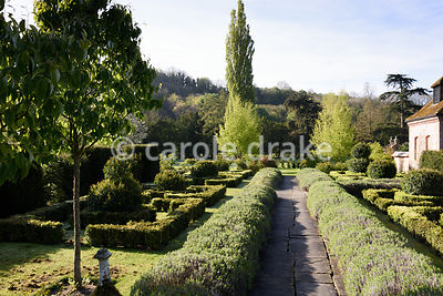 A stone path runs between clipped lavender and box and laurel topiary in the formal garden at Heale House, Middle Woodford, W...