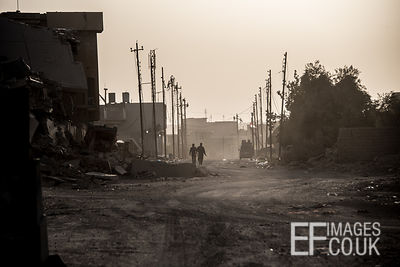 Federal Police walk down a damaged street near the frontline at sunset. West Mosul, Iraq, 5th June 2017