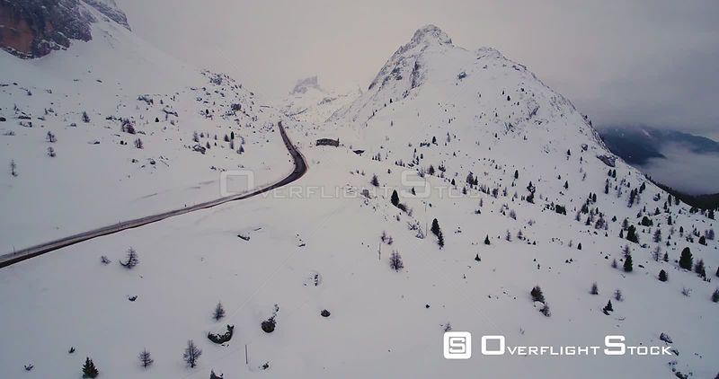 Aerial, a car driving on a road in snowy mountains with a beautiful view on mountain tops