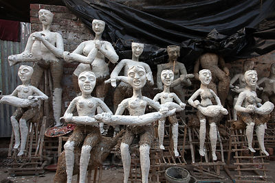 Idols for the Kali Puja festival being made in Kumartoli (Potter's Town), Kolkata, India. They're hand-made from straw forms ...