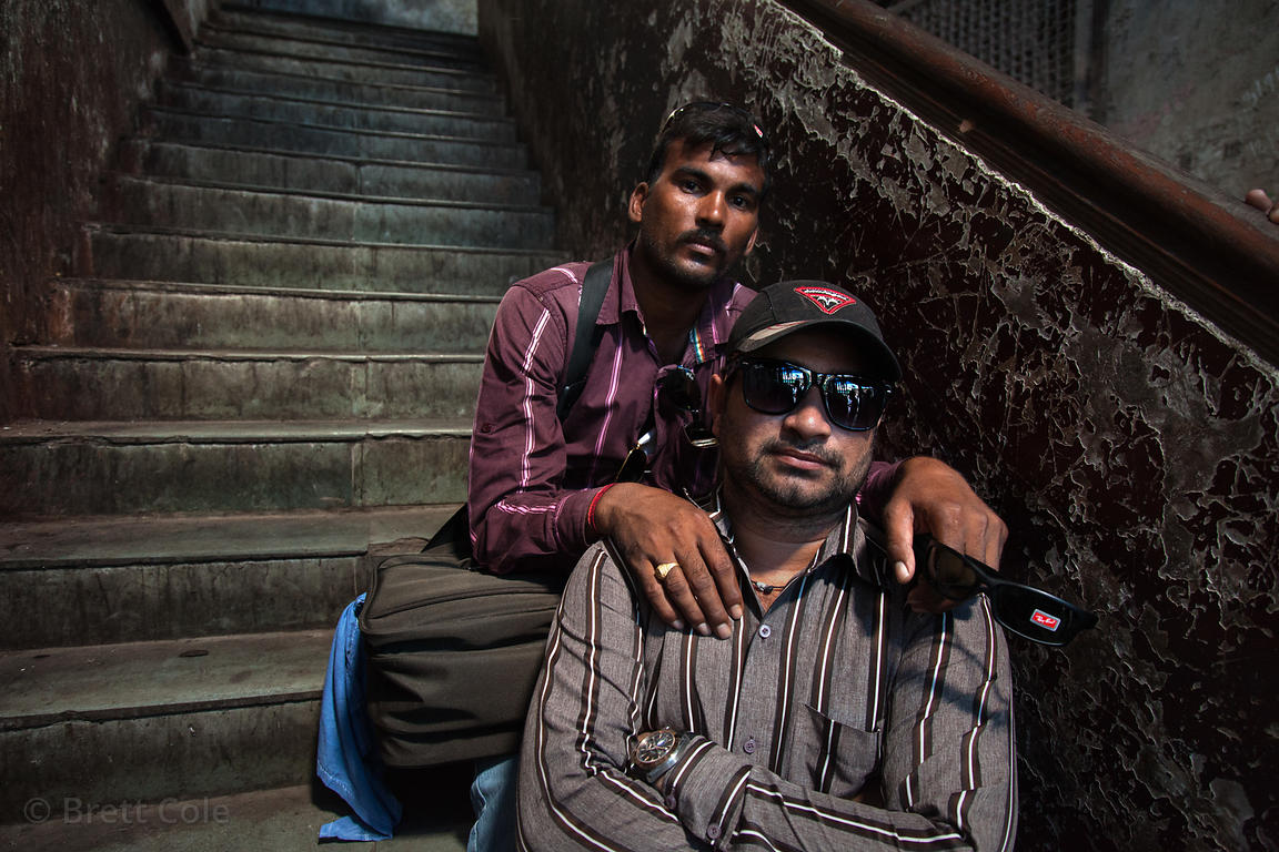 Portrait of two men in a darkened stairwell of a housing unit in Lalbaug, Mumbai India.