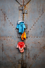 A baby's clothes hang out to dry on a large metal door, Sovabazar, Kolkata, India