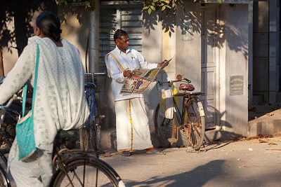 A man reads his newspaper on the streets of Pondicherry, India