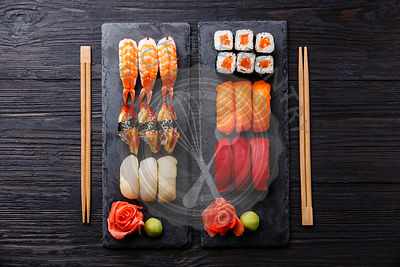 Sushi rolls, maki, nigiri Set served for two on black stone slate on dark wooden background