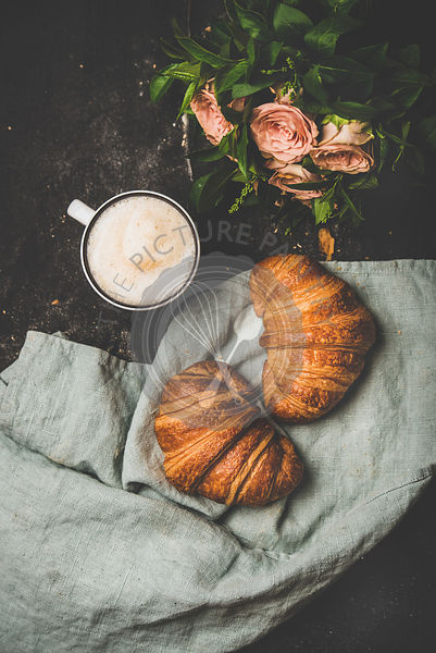 Cup of cappuccino, fresh croissants and flowers over shabby background