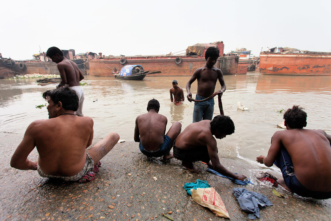 Men bathe near ships on the Hooghly River near Princep Ghat, Kolkata, India.