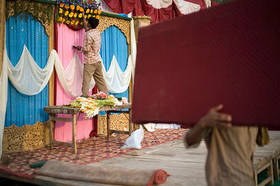 India - Delhi - Workers prepare the stage for a wedding and a florist creates a floral decoration on a canopy above which the...