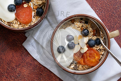 Healthy breakfast of bircher muesli, dried apricots, blueberries and youhurt in breakfast mugs.
