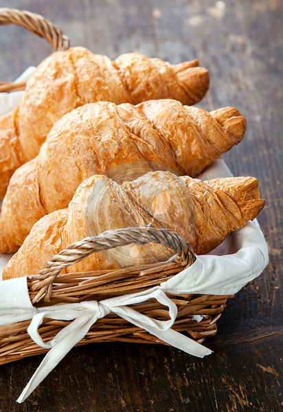 Croissants in basket on wooden table