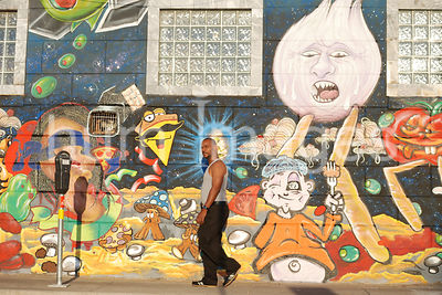 African American Man walking in front of a mural in Deep Ellum