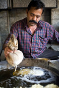 India - Delhi - A man squeezes batter from a cloth to make jalebis at the Old and Famous Jalebi Wala (at the corner of Dariba...