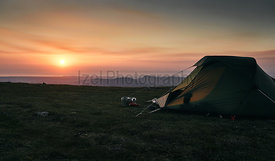 A tent pitched on Scoat Fell as the sun sets over Ennerdale In the English Lake District, UK.