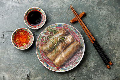 Spring rolls with sauce on stone background