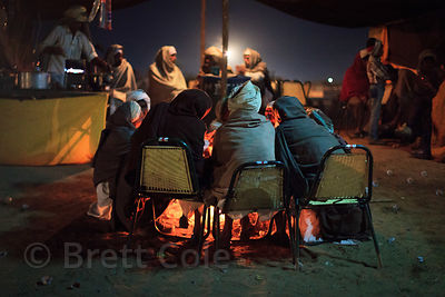 Camel herders and Hindu pilgrims at night in Pushkar, India. Taken during the camel mela and Kartik Purnima.
