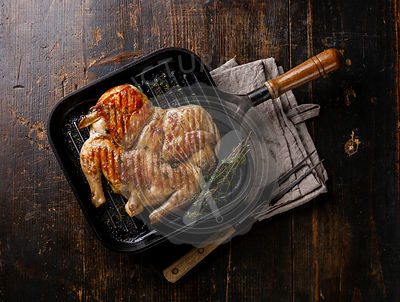 Grilled fried roast Chicken Tabaka in frying pan on wooden background