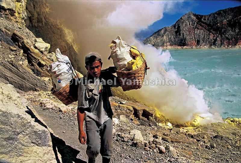 Workers carry loads of sulfur, some weighing up to 175 lbs (80 kg), making three trips in a ten-hour day to the top of the vo...