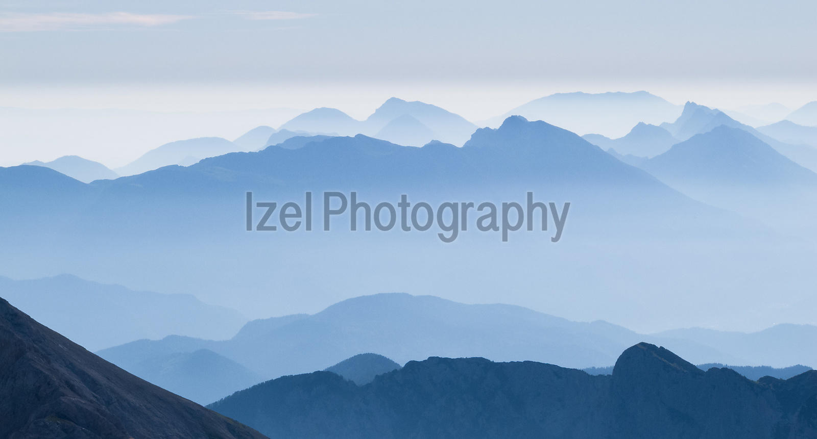 A misty dawn over the Triglav National Park turns the mountains blue. Taken from the summit of Triglav.