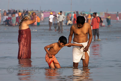 A father and son bathe in the Bay of Bengal during the Gangasagar Mela, Sagar Island, India.