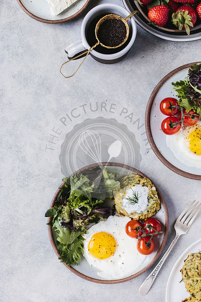 A fried egg, green salad, and a zucchini fritter