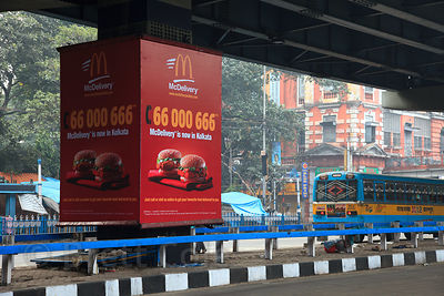 Sign for McDonalds McDelivery with a 666 contact number, near Newmarket, Kolkata, India.
