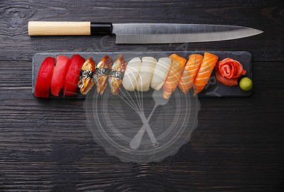 Nigiri Sushi set on stone slate and Japanese knife on dark wooden background copy space