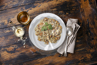 Risotto with chanterelle mushroom on plate on wood table background