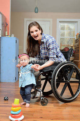 Young woman using a wheelchair playing with her baby